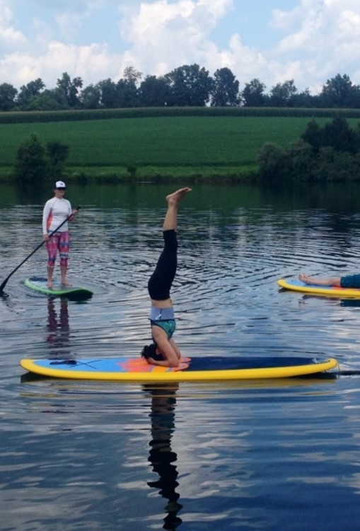 Erika doing a headstand on a paddleboard.