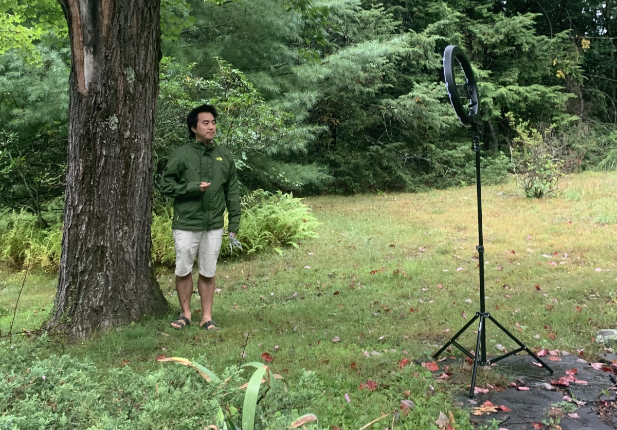 Albert Kim standing by a tree with a recording device in front of him