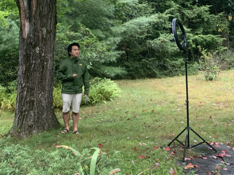 Albert Kim next to a tree and in front of a recording device